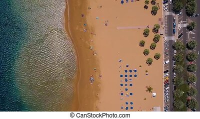 View from the height of the golden sand, palm trees, sun loungers, unrecognizable people on the beach Las Teresitas, Tenerife, Canaries, Spain. Timelapse