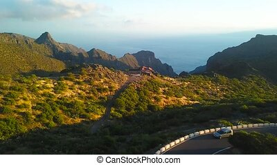View from the height of the rocks, winding road and ocean in the distance in the Masca at sunset, Tenerife, Canary Islands, Spain.