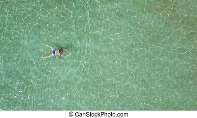 View from the height on swimming woman in the clear sea -...