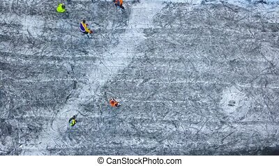 View from the height on unrecognizable people playing hockey in the winter outdoors