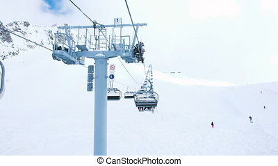 View from the open lift in motion upstairs, four-seat lifts work at the ski resort, downhill skiing and snowboarding tourists, slow motion.