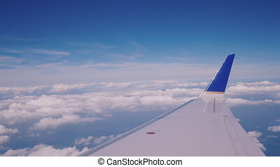 View from the passenger seat of the airliner to the wing and clouds