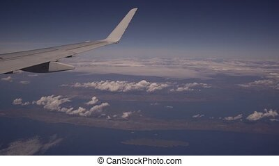 View from the plane to the island of Hvar in Croatia. Aerial view of beautiful white heap clouds on blue sky. Wing of an airplane from a porthole. Travel concept