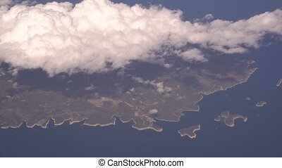 View from the plane to the island of Vis in Croatia. Aerial view of beautiful white heap clouds on blue sky. Wing of an airplane from a porthole. Travel concept