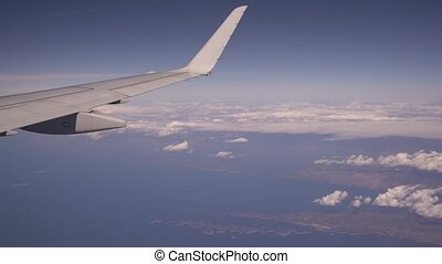 View from the porthole of the passenger plane. The plane flies over thick clouds, the camera shows the wing, The concept of travel and a rich life