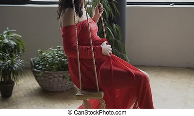 View from the pregnant woman who in a long red dress swinging on the swing near the big window. Conception of pregnancy - soon mother, motherhood, family