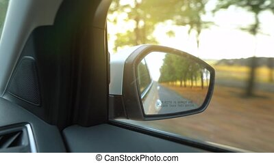 View from the rearview mirror as car drives through the road surrounded by trees at sunset