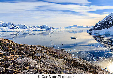 View from the rocky coast to the Neco bay surrounded by glaciers and mountains and cruise ship standing still on the sea surface, Antarctic