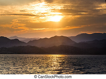 View from the sea on the distant shore with the setting sun over the mountains.