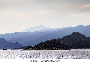 View from the sea to the coast with a small fortress on the top of the mountain.