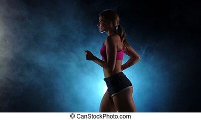 View from the side on the running girl on a smoky black spotlight background. Slow motion