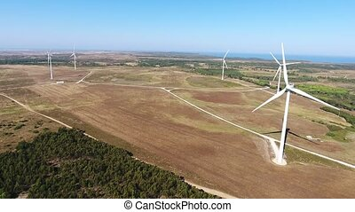 View from the sky, wind power generators. Ocean in the background.