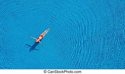 View from the top as a woman in a red swimsuit swimming and lying on her back in the pool. Relaxing concept