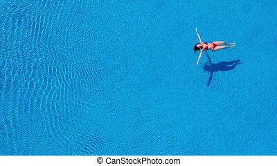 View from the top as a woman in a red swimsuit swims backstroke in the pool