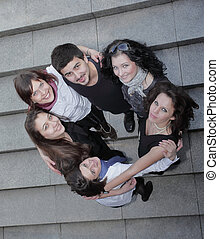 happy group of students standing on the stairs
