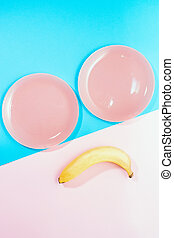 view from the top Lay Flat. the concept of Breakfast, healthy food. keto diets. free space for text, copy space, minimalism. two pink plates and two bananas on a pink blue background. sad smile