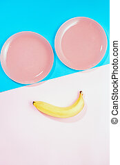 view from the top Lay Flat. the concept of Breakfast, healthy food. keto diets. free space for text, copy space, minimalism. two pink plates and two bananas on a pink blue background. cheerful smiley face, happy mood