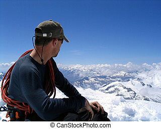 View from the top - Mountaineer absorbing the view from the...