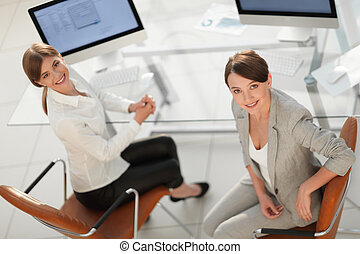 view from the top. two women colleagues sitting near the...