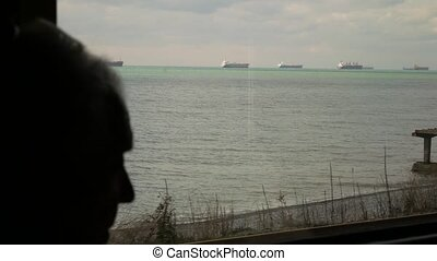 view from the train window. ships at sea. silhouette of a passenger in a train window. 4k.