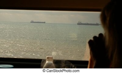 view from the train window. ships at sea. silhouette of a...