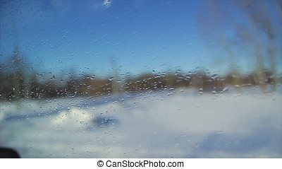View from the window of a moving car on a winter snowy road through the forest, winter in Russia