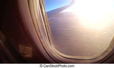 View from the window of a passenger airplane during sunset on a landscape and horizon.
