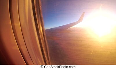 View from the window of a passenger airplane during sunset...