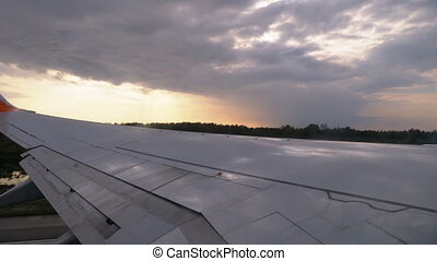 View from the Window of a Passenger Plane on the Wing during Take-off at Sunset