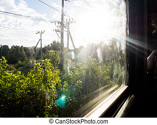 view from the window of a train, partly blurred, on a Sunny day