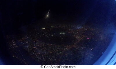 View from the window of an Jet Airplane flying low over the city at night