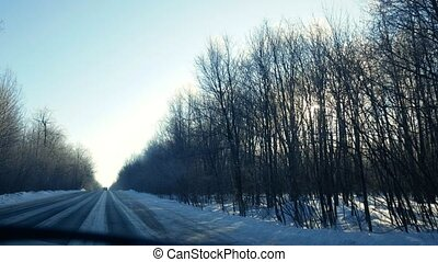 View from the window of the car moving on a bright sunny winter road