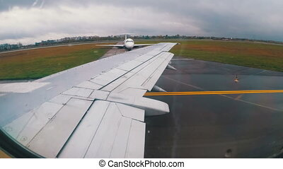 View from the Window on the Wing of an Airplane moving along the Runway at Airport