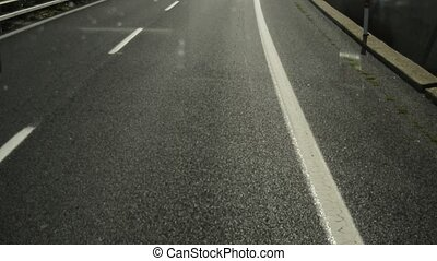 View from the windshield of the car on the highway with markings, fast movement and blurred focus