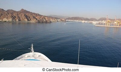 view from top deck of cruise ship sailing to city in...