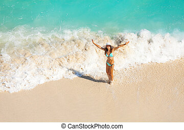 View from top of girl with hat in ocean waves