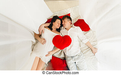 View from top of happy pregnant couple lying on bed