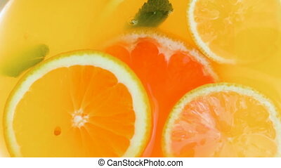 View from top of lemonade jar with floating oranges,...