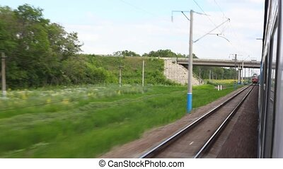 view from train going past electric locomotive coming from opposite direction