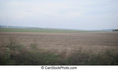 View from train - wind energy turbine at background of autumn meadows