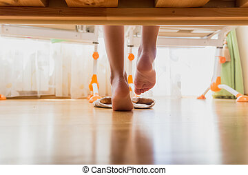 View from under the bed on girl stepping on wooden floor