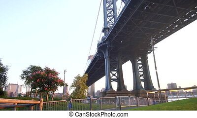 View from under the Brooklyn Bridge in New York City USA on Sunny Day Green Grass with Sunlight