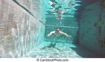 View from water on the young sports man floating under water in the pool