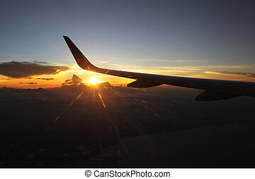 aircraft wing flying over beautiful sunlight