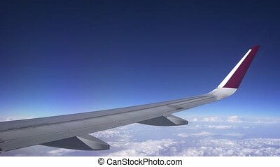 Wing and fuel pods of a commercial airliner over a coudy, overcast horizon, taken from a passenger window perspective. Ultra HD stock footage