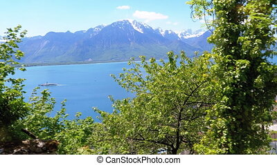 View from the Window of a Mountain Train on Montreux City, Lake Geneva, Swiss Houses in Village and Alps. Landscape beautiful view from the height of embankment, on sunny day. Rise of the train at the Big slope. Train in Steep Mountains Driving Uphill.