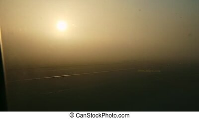 view from window on airplane ride by empty runway against sunrise with fog