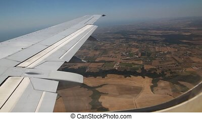 View from window on wing of plane flying over fields landscape