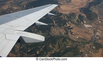 View from window on wing of plane flying over mountains landscape