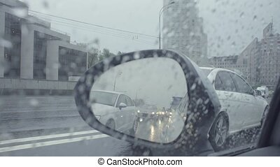 View in car's rearview mirror on the city street. - Point of...
